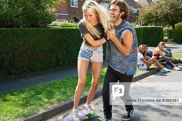 Junges Paar übt mit Skateboard