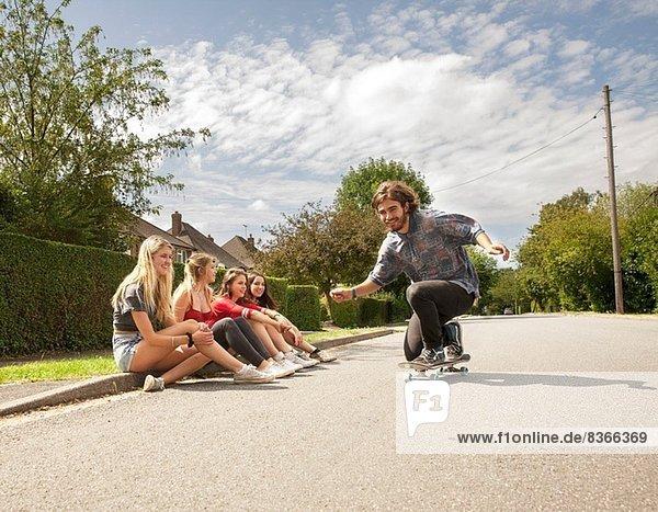 Vier junge Frauen sitzen auf dem Bordstein und schauen Skateboardern zu.