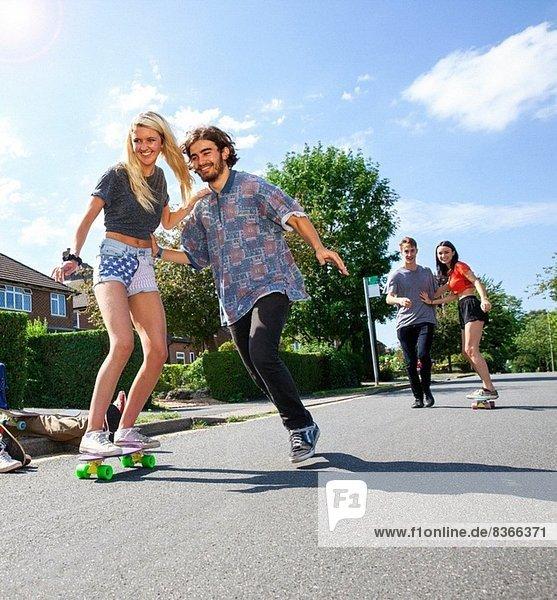 Zwei junge Paare mit Spaß auf Skateboards