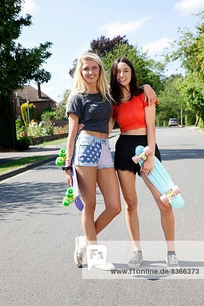 Portrait of two young women with skateboards