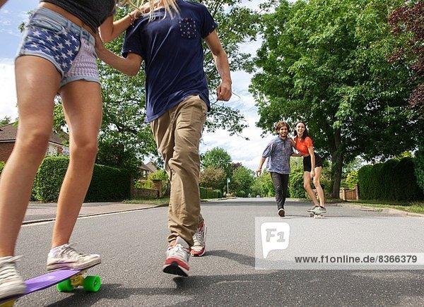 Zwei junge Paare skateboarden auf der Straße