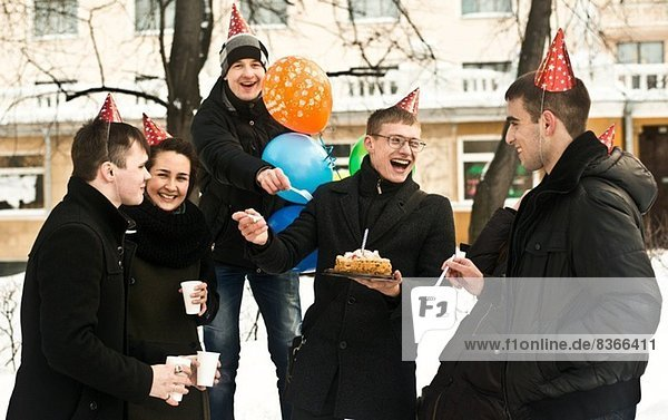 Gruppe junger Freunde auf der Stadtstraße mit Geburtstagskuchen