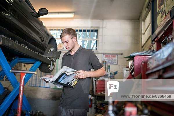 Mechanic reading manual in garage
