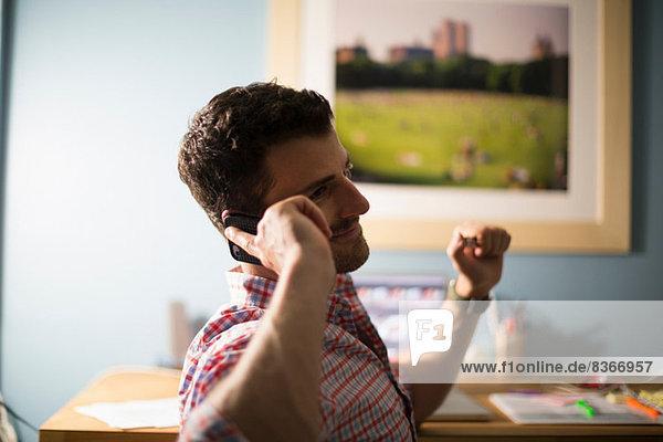 Mann sitzt am Schreibtisch mit Smartphone