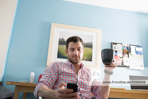 Man sitting at desk with smartphone and coffee cup