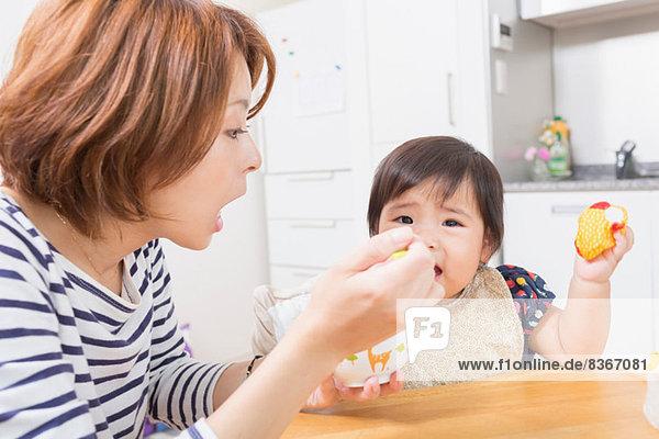 Mutter füttert Baby in der Küche