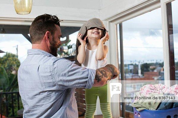 Vater und Kleinkind sortieren Wäsche  Kleinkind mit Kleidung auf dem Kopf