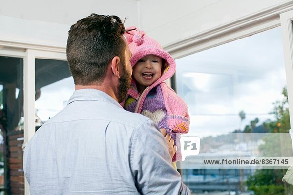 Vater Dressing Tochter in Kapuzenstrickjacke