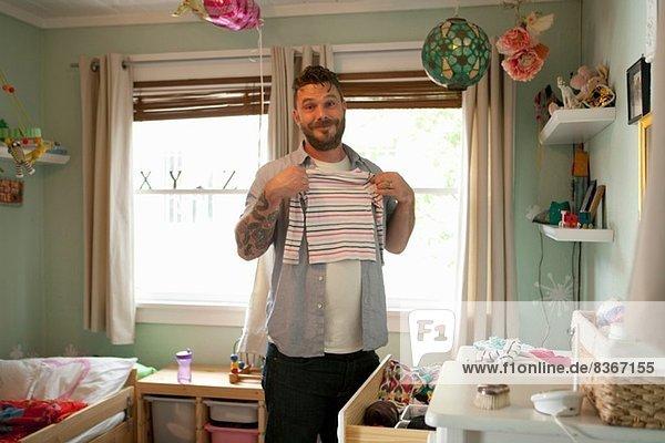 Vater legt Kinderwäsche weg