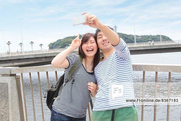 Junges Paar beim Selbstporträtfotografieren mit dem Smartphone