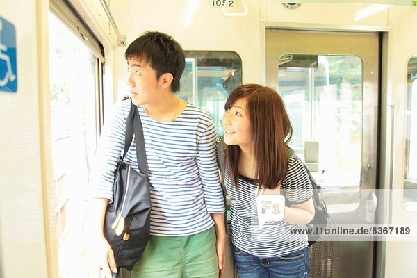 Junges Paar im Zug stehend  durchs Fenster schauend