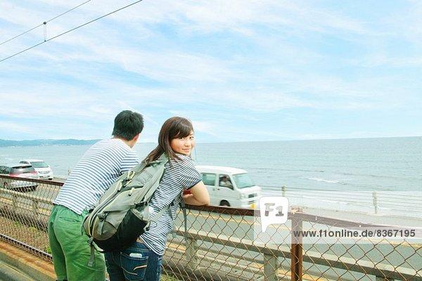 Junges Paar lehnt am Zaun und schaut aufs Meer
