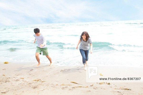 Junges Paar läuft vor der Flut davon