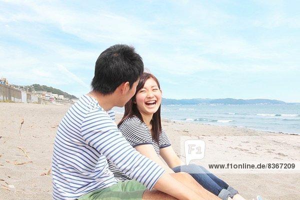 Junges Paar sitzt am Strand und lacht.