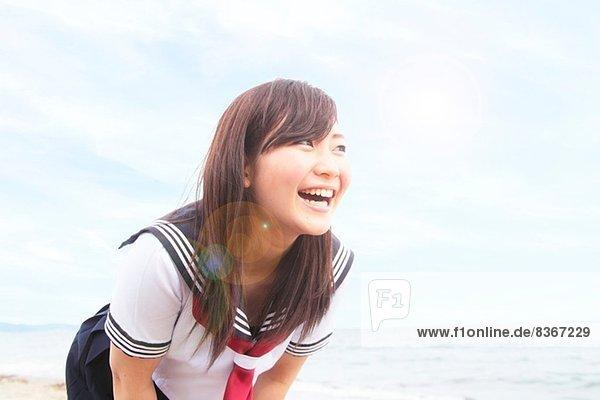 Junge Frau  die sich nach vorne lehnt und lacht.