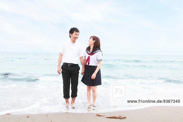 Junges Paar in Schuluniform stehend am Sandstrand