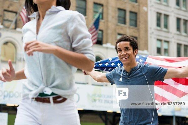 Mann mit amerikanischer Flagge läuft der Frau nach