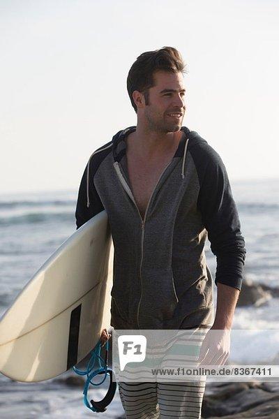 Young man carrying surfboard  San Diego  California  USA