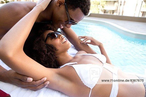 Porträt eines jungen Paares am Pool