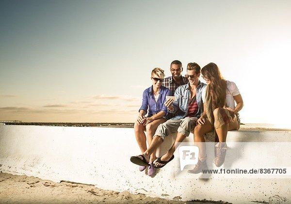 Freunde sitzen an der Wand mit Smartphone  Mission Beach  San Diego  Kalifornien  USA