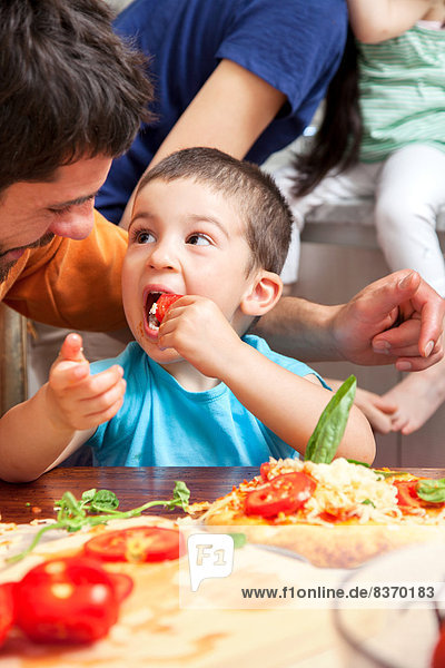 Boy eating homemade pizza toppings