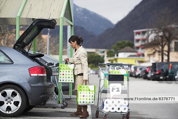 Frau Auto Tasche beladen parken kaufen