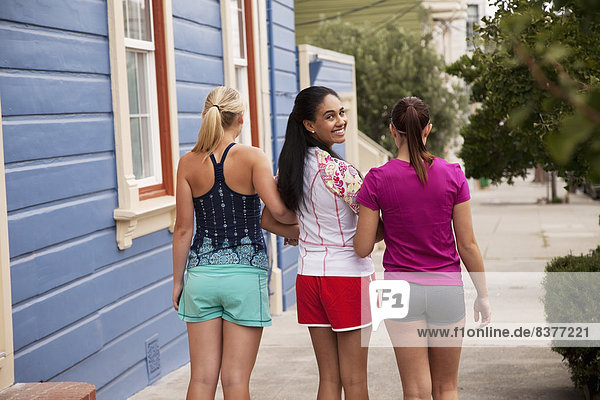 Three Young Female Friends Walking Arm In Arm  California  Usa