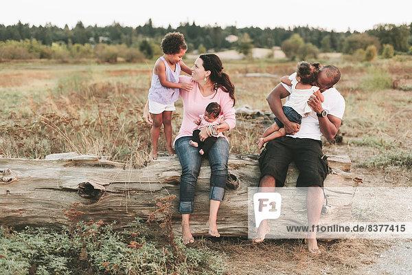 Interracial Family Sitting On Log On Beach  British Columbia  Canada
