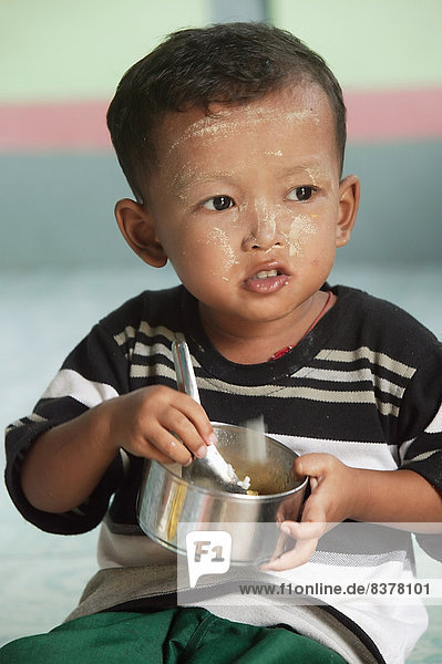 A Child Eating In Preschool Centre Myanmar