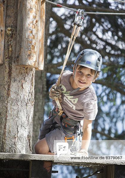 Kleiner Junge im Klettergarten