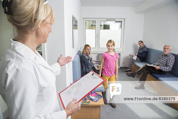 Sprechstundenhilfe ruft eine Patientin auf  Wartezimmer in einer Zahnarztpraxis  Deutschland