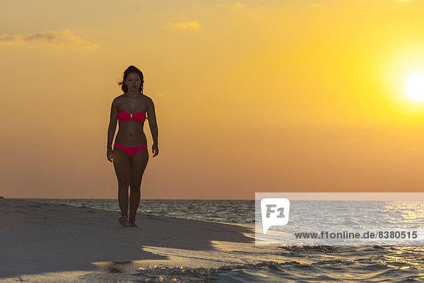 Frau läuft am Strand bei Sonnenuntergang  Indischer Ozean  Malediven