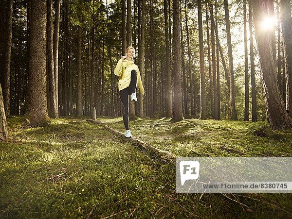 Frau macht eine Fitnessübung auf einem umgefallenen Baumstamm im Wald  Tirol  Austria