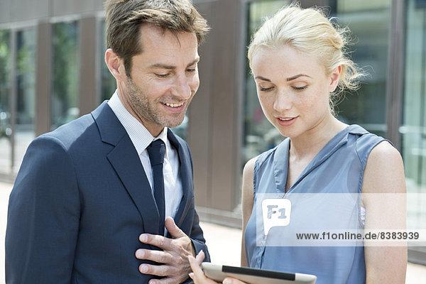 Immobilienmakler mit digitalem Tablett  um dem potentiellen Käufer die Immobilie zu zeigen.