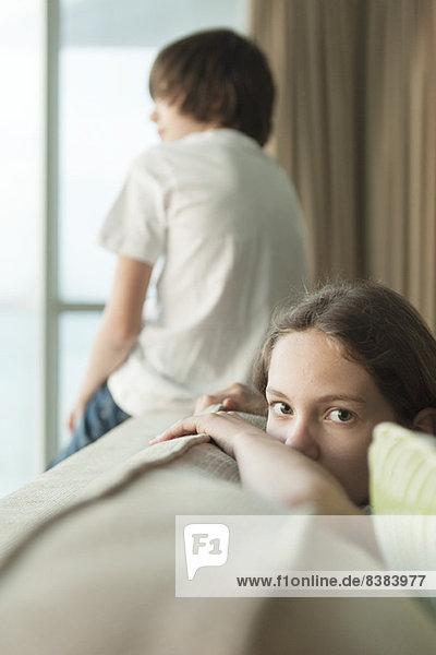 Mädchen auf Sofa sitzend mit Kopf auf dem Arm  Bruder mit Blick aus dem Fenster im Hintergrund