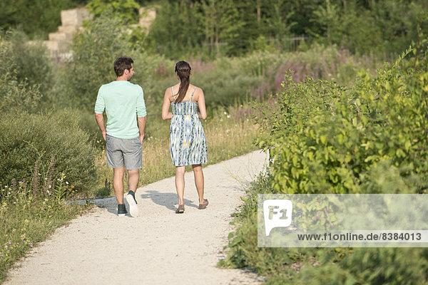Paar auf Spaziergang durch den Park  Rückansicht