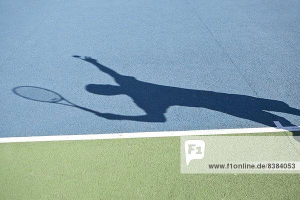 Schatten des Tennisspielers  der den Ball serviert.
