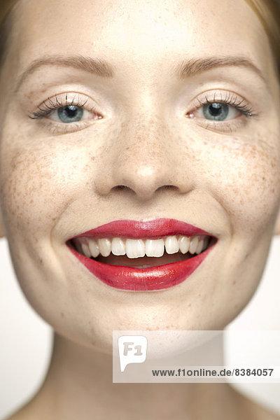 Junge Frau mit rotem Lippenstift  lächelnd  Portrait