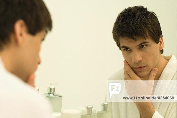 Mann im Bademantel im Spiegel  berührendes Gesicht
