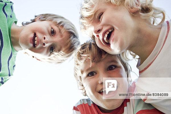 Jungen kauern sich zusammen  lächeln vor der Kamera.