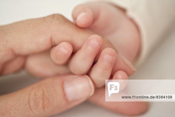 Baby und Mutter halten sich an den Händen  abgeschnitten  Nahaufnahme