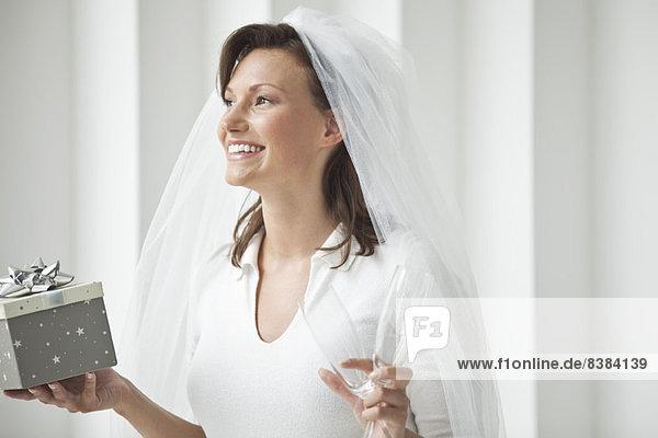 Braut mit Sektflöte und Geschenkbox