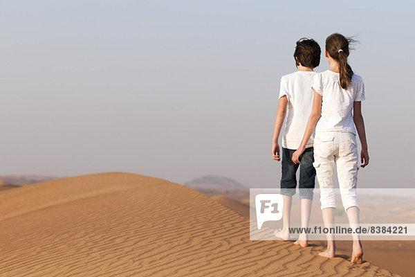 Geschwister wandern auf Sanddüne  Rückansicht