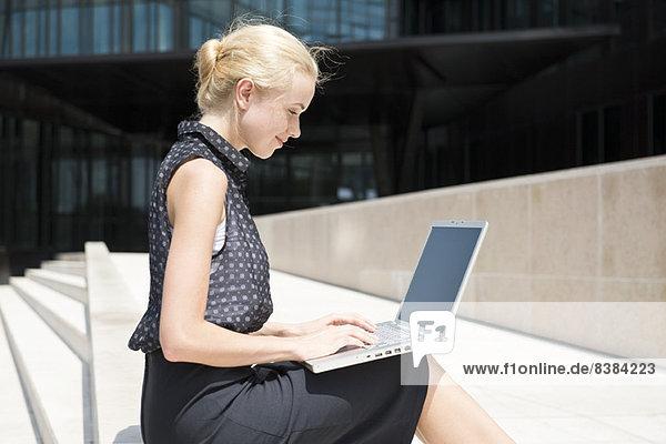 Geschäftsfrau mit Laptop bei der Arbeit im Freien