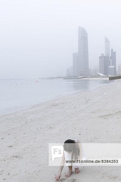 Mädchen auf der Suche nach Muscheln am Strand