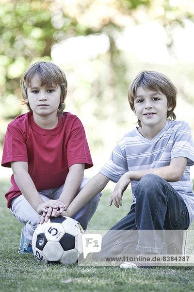 Jungen hocken auf dem Spielfeld mit Fußball  Portrait
