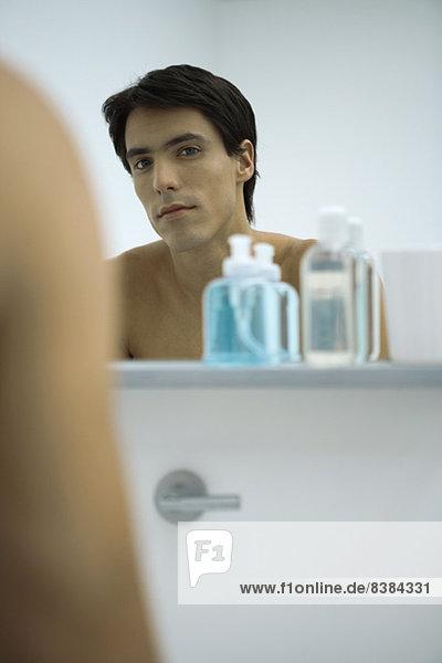 Mann schaut sich selbst im Spiegel an