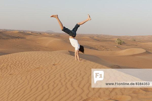 Teenager-Junge beim Handstand in der Wüste