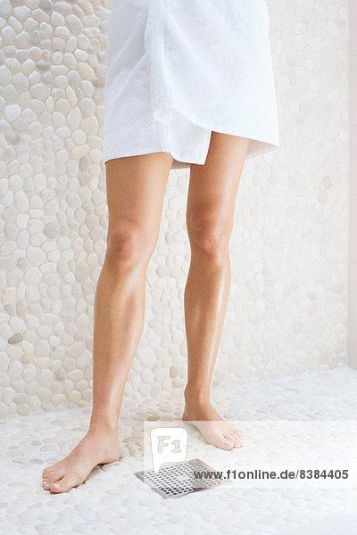 Frau in Handtuch gewickelt im Duschraum stehend  niedrige Sektion