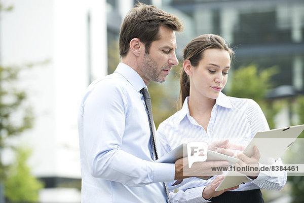 Geschäftspartner  die mit digitalen Tabletts zusammenarbeiten